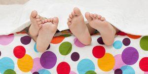 piedi che sporgono dal letto